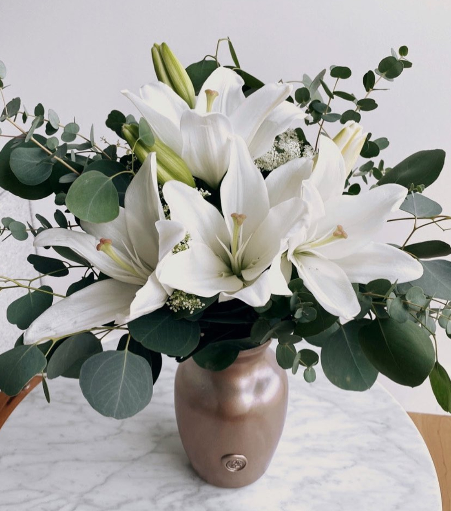 Fresh lilies and eucalyptus arrangement in rose gold jar on marble table
