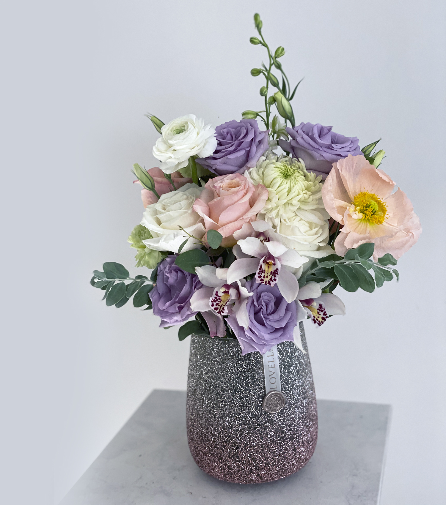 Rosey pastel fresh floral arrangement in glimmering jar on marble table