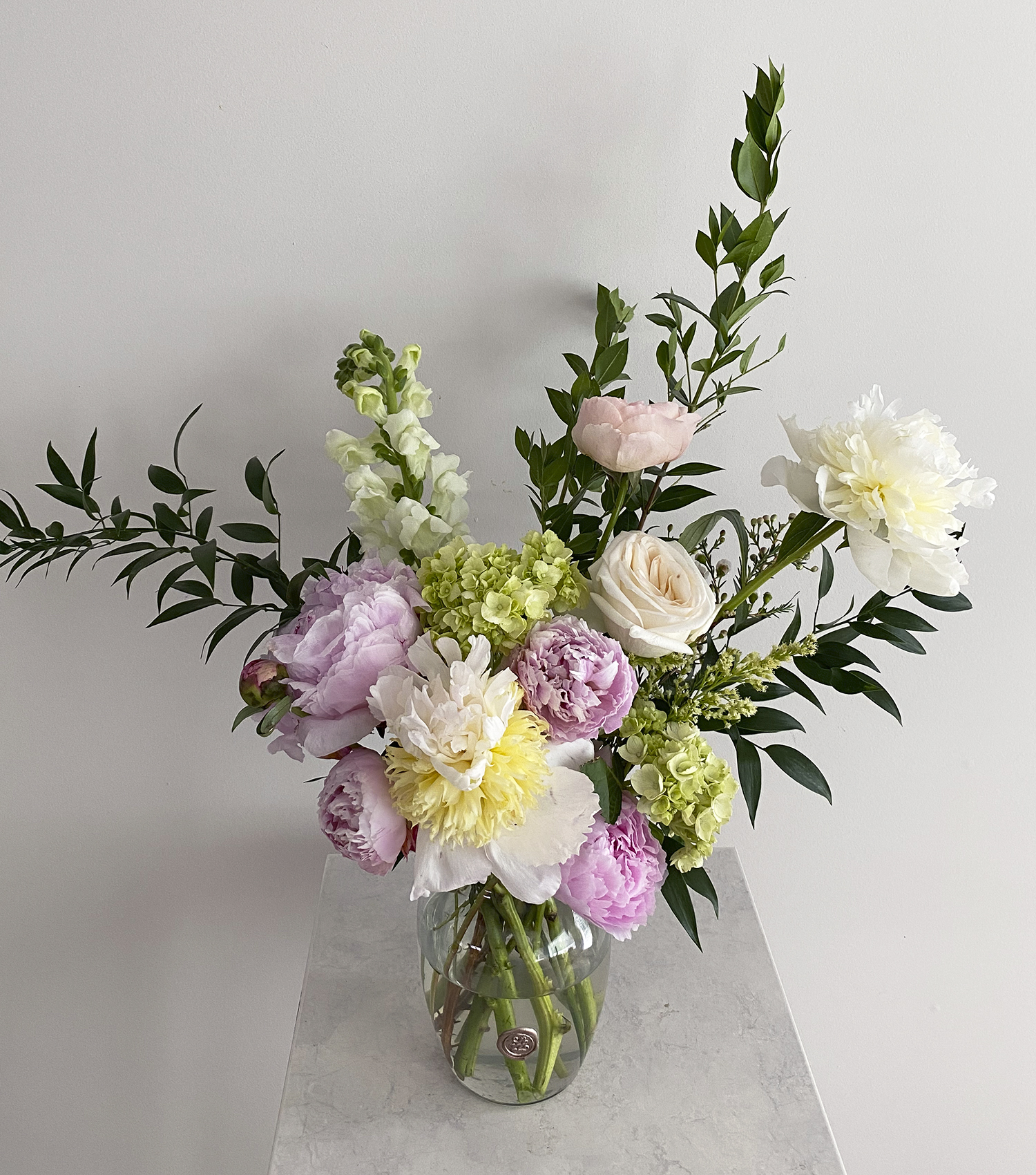 Gorgeous fresh floral arrangement in clear glass vase on marble table